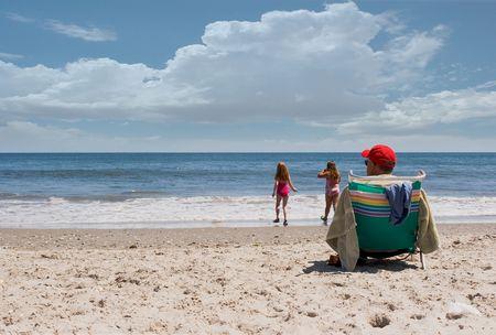 ビーチで彼の孫を見守る祖父。