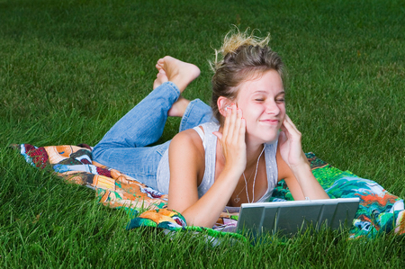 A young girl relaxing with her mp3 player and laptop