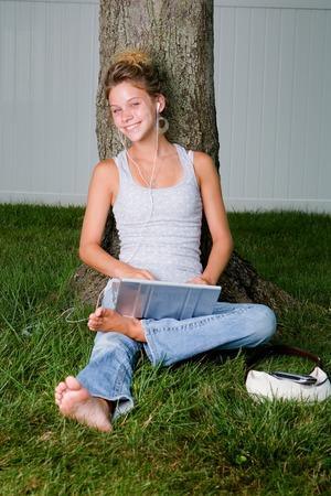 그녀의 MP3 플레이어 및 노트북 편안한 젊은 여자 스톡 콘텐츠
