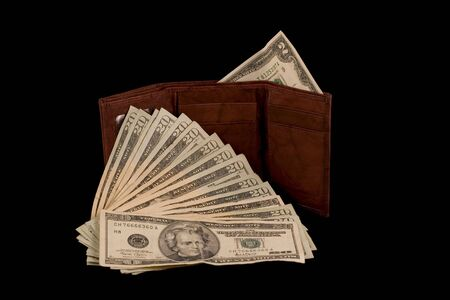 Wallet with a two dollar bill and some twenties isolated on black