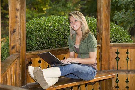 Eine schöne blonde Teenager-Mädchen mit ihrem Laptop in den Park Standard-Bild - 3741293