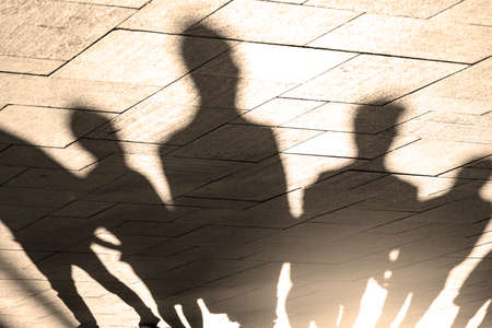 Shadows and silhouettes of people at a city during sunset Stock Photo