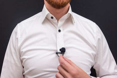 A man dressing in white shirt holding small lavalier microphone