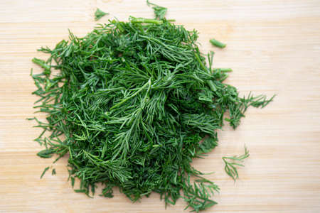 Close-up top view of chopped fresh green dill, cut dill on wooden board in kitchen