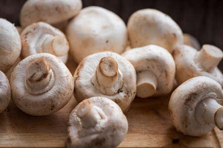 Fresh dirty agaricus or shampignon mushroom before peel on the wooden table