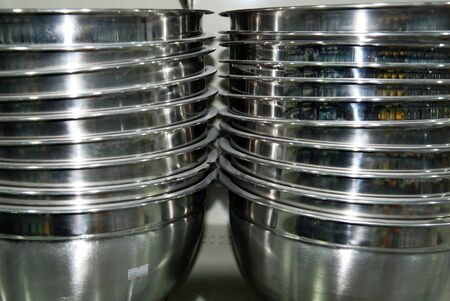 stainless steel cooking bowls stacked in shop shelf