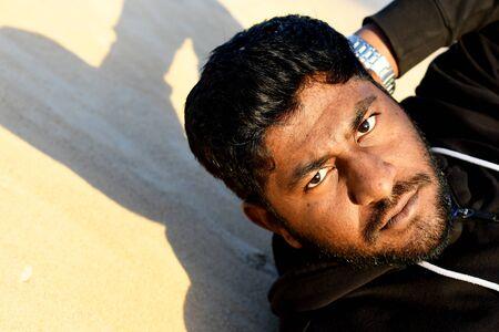 Man with black eyes sunburned skin
