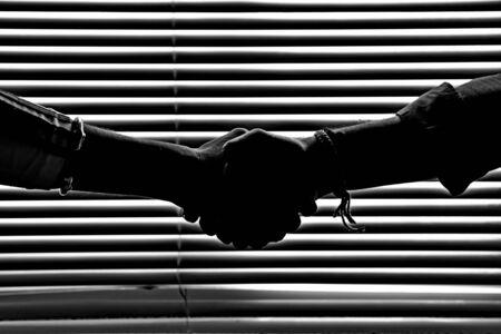 Hands shaking in dark figure silhouette in front of a striped window light