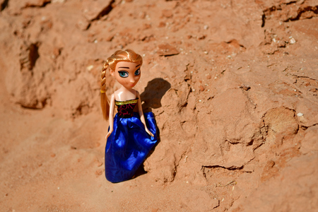 Blue satin dress on model Barbie posing in the rocky area Stock Photo
