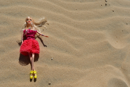 blonde doll posing on the sand in her red hot dress Stock Photo