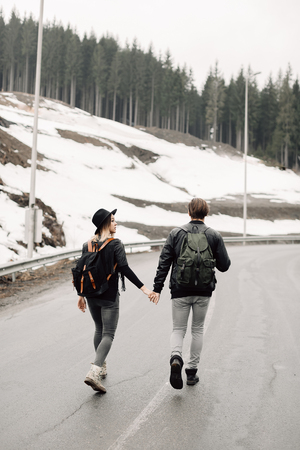 the couple are traveling. Boy and girl with backpacks travel. The couple walks along the path. Happy couple holding hands