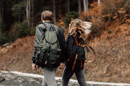 couple are traveling. Boy and girl with backpacks travel. The couple is on the road. Exclusive backpacks on the back. Flowing hair fluttering in the wind Stock Photo