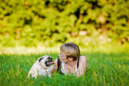 Nice blonde and cheerful young woman with her dog resting on green lawn in the park  photo