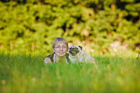 Nice blonde and cheerful young woman with her dog resting on green lawn in the park. photo