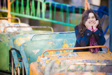 carrousel: A teenage girl smiling and sitting on an old carrousel in a park.