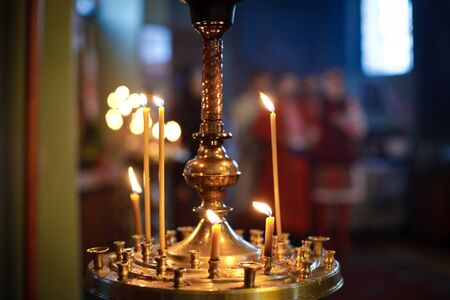 russian ethnicity: Burning candles in a Russian ortodox church. Close-up of ordinary church interior. Selective focus.