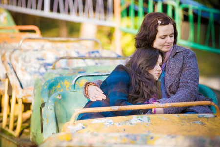 carrousel: Woman and her teenage daughter embracing and sitting on an old carrousel in a park. Stock Photo