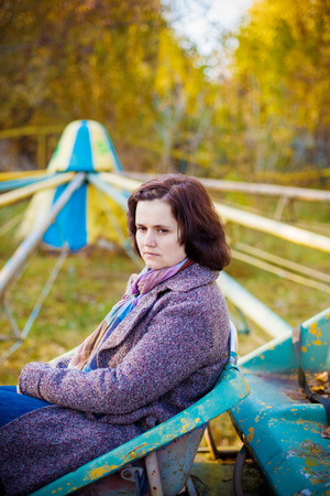 reverie: Woman sitting on an old carrousel in an autumn park. With copy space. Stock Photo