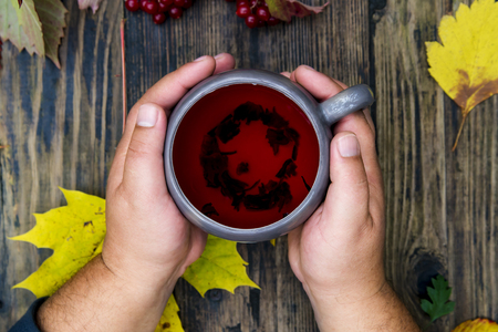 male hands hold a cup with red tea against the background of a wooden table and autumn leaves Stock Photo