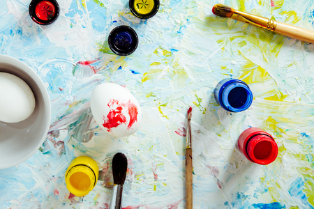 brushes, paints, the eggs on an art table made for painting of Easter egg, the top view, a close up Banque d'images - 124695185