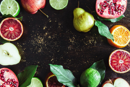 the red oranges, lime, apples, pears, pomegranate cut on pieces and whole lie on the wooden dark background strewed with cocoa, close-up