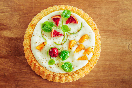 gentle magnificent biscuit with vegetable vanilla cream decorated with fruit, a bud of a rose and young leaves on a wooden table, the top view, a close up