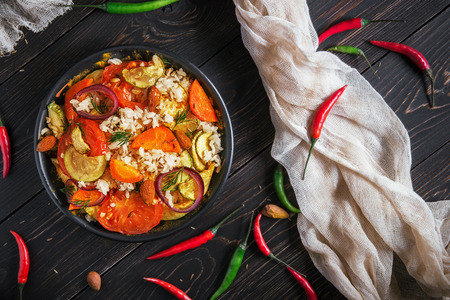 the Indian rice and vegetables pilaf with spices in a clay plate on a wooden table with hot multi-colored pepper, top view Stock Photo