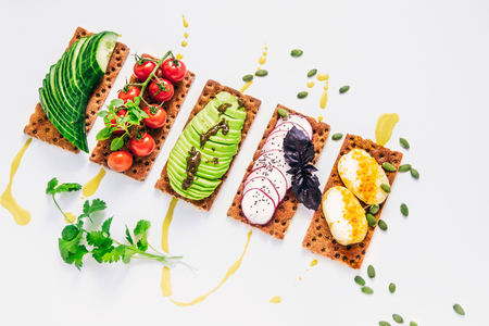 easy sandwiches on the crackling wholegrain toast with avocado, cherry tomatoes, a cucumber, a garden radish, new potato with paste from flax seeds, chia seeds, a turmeric, a basil and drops of vegetable oil on a white background with cilantro and seeds of pumpkin Stok Fotoğraf