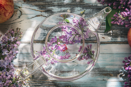 lilac flowers in a transparent glass teapot on a blue old wooden table, the top view, a close up
