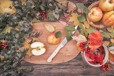 Pommes sur une table en bois recouverte de feuilles d'automne jaunes avec une tasse de thé chaud et de baies de kalina, vue de dessus