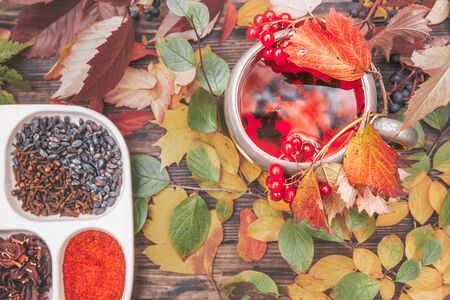 Cup of hot tea scaffold on a wooden table with autumn yellow and red leaves, top view