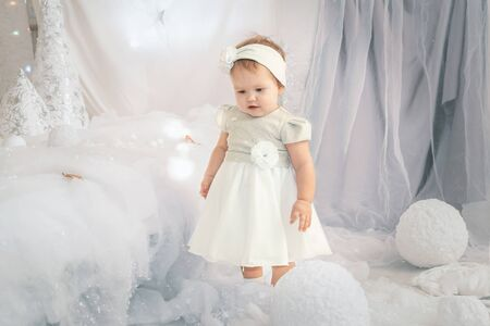 Little girl stands against the background of New Year s decorations