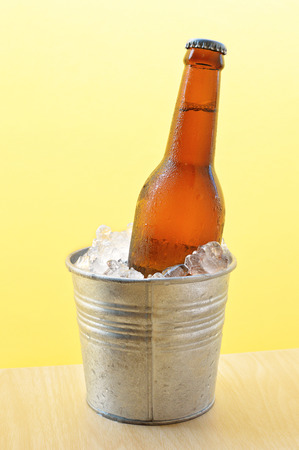 Glass bottle of beer in metal bucket isolated on wood table