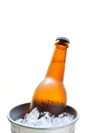 Glass bottle of beer in metal bucket isolated on white background