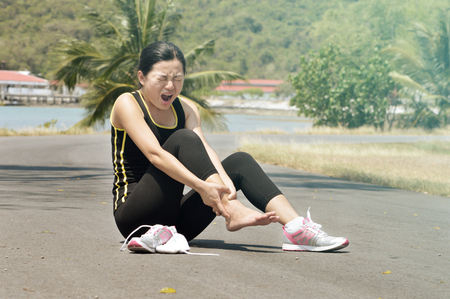 soreness: Sports injury. Woman with pain in ankle while jogging Stock Photo