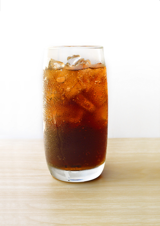 Cola in glass with ice cubes on wood table