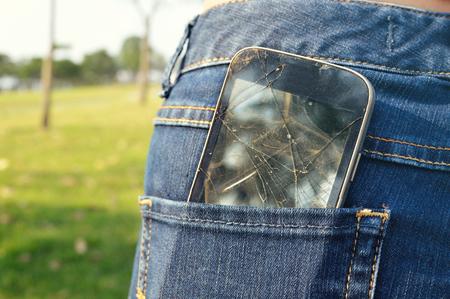 Black smart mobile phone in jeans pocket Stock Photo