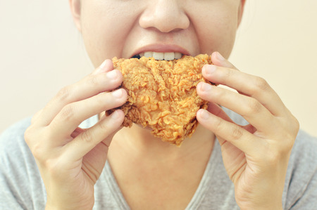 Young  woman holding and eating fries chicken, vintage tone image Stock Photo