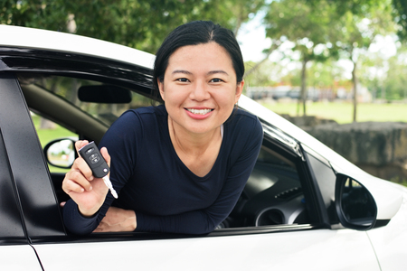Young asian woman shows the keys to her new car Stock Photo