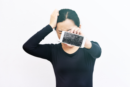 Sad woman showing broken smartphone with crashed screen. Stock Photo