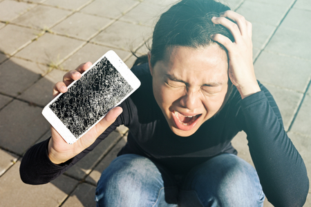 Screaming woman  holding a screen crack the smartphone outdoor. Reklamní fotografie - 81036339
