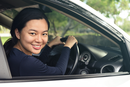 Young woman in casual wear looking over her shoulder while driving a car