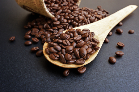 Roasted coffee beans in a wooden spoon