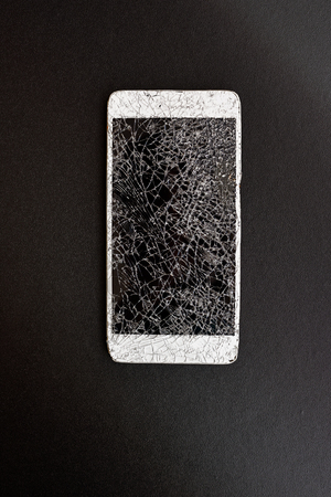 Smart phone with broken screen  on black background. Stock Photo