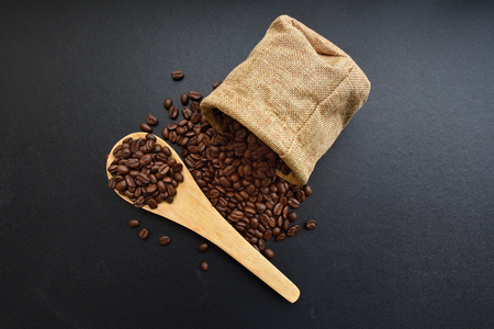 Roasted coffee beans from a sack on a black background. Stock Photo