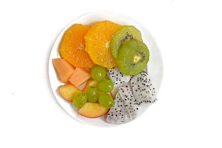 Plate of healthy fresh fruit salad on white background. Top view.