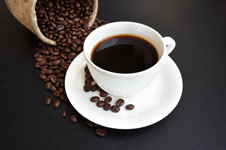 Coffee cup and coffee beans on a dark background. Stock Photo