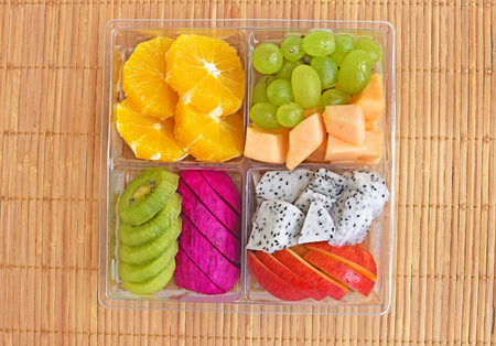 Fruit in takeaway plastic box on wood background Imagens - 83478687