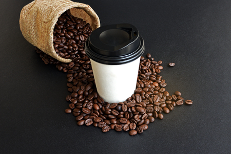 Takeaway coffee in paper cup and coffee beans on black table Stock Photo
