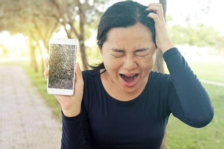 Sad woman is holding smartphone in her hand with broken screen